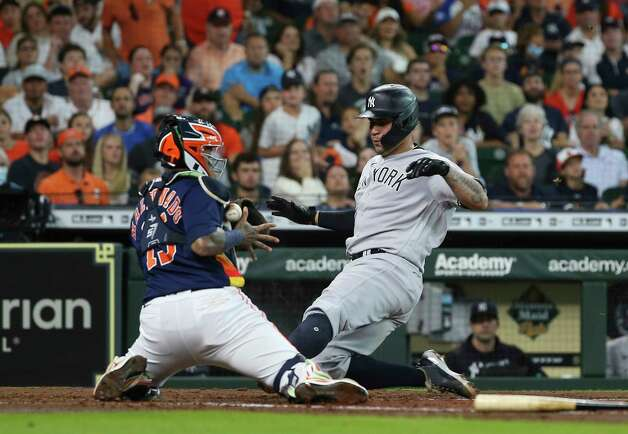 The ball bounces off of Houston Astros catcher Martin Maldonado's glove as New York Yankees catcher Gary Sanchez (24) is sliding into the home plate and scores during the top third inning of the MLB game Sunday, July 11, 2021, from Minute Maid Park in Houston. Photo: Yi-Chin Lee, Staff Photographer / © 2021 Houston Chronicle