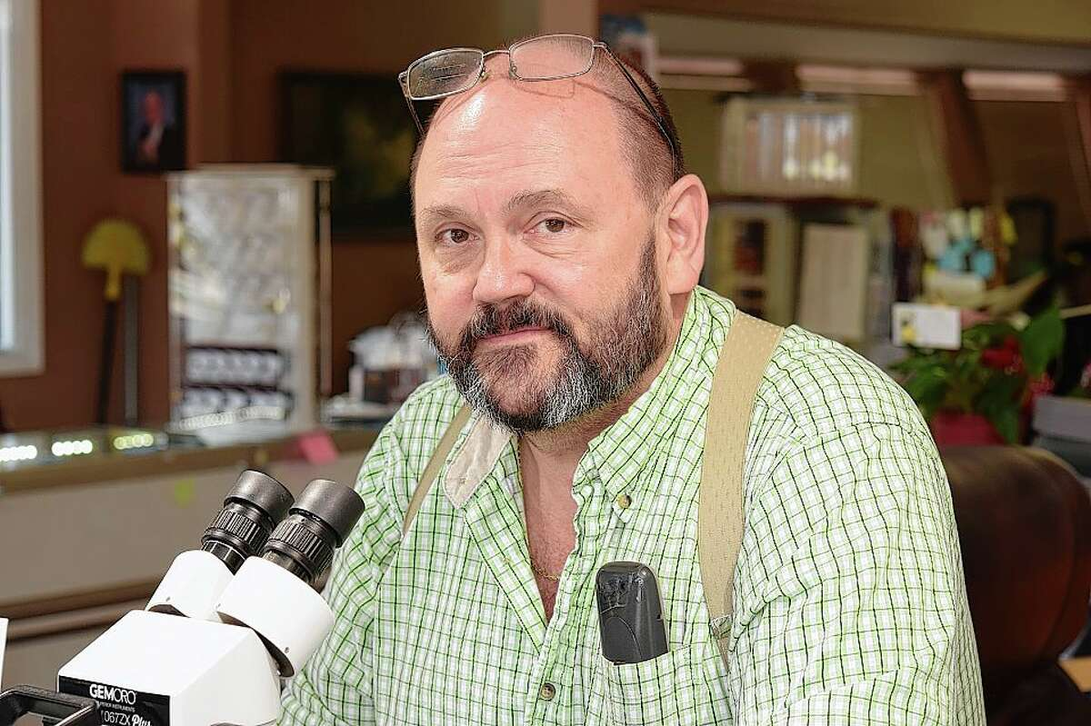 Kevin Denney spends much of his work time looking at jewelry under a microscope.