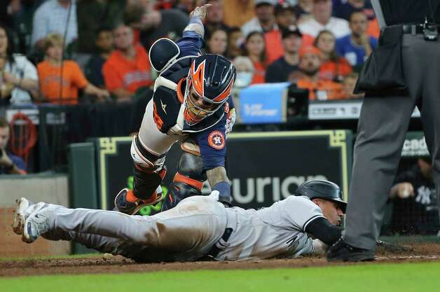 New York Yankees shortstop Gleyber Torres (25) is safe as Houston Astros catcher Martin Maldonado (15) is trying to tag him out at home plate during the top seventh inning of the MLB game Sunday, July 11, 2021, from Minute Maid Park in Houston. Photo: Yi-Chin Lee, Staff Photographer / © 2021 Houston Chronicle