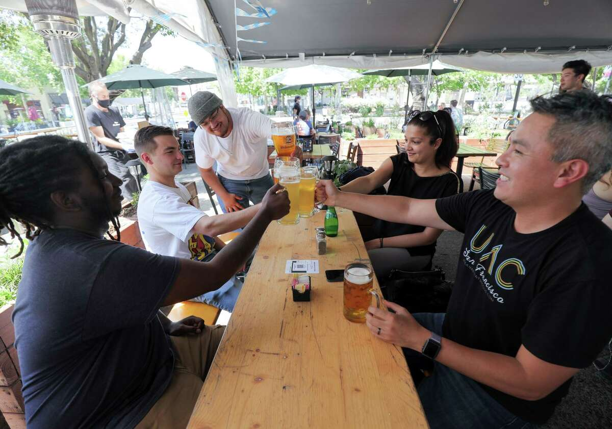 Andy Huang, at right, clinks glasses with friends at Olympus in Mountain View on Saturday. Members of the Urban Adventure Club of San Francisco utilized Caltrain as their transport as they hopped from pub to pub.