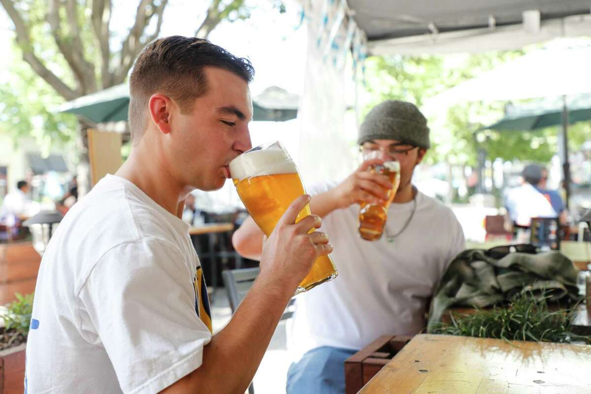 Austin Lau, 22, at left, and Tanner Franco, 24, both of San Mateo, drink Das Boots at Olympus in Mountain View on Saturday.