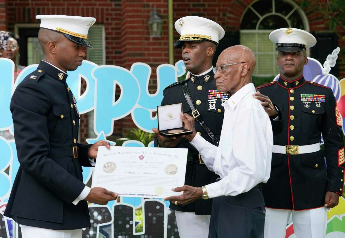Marine Capt. Ibrahim Diallo, left, Maj. Courtney Boston, center, and Sgt. Major James Cabarrus, right, present Arthur Jackson, 99, with a replica Montford Point Marines Congressional Gold Medal during a ceremony Saturday, July 10, 2021 in Spring. Jackson was one of the Montford Point Marines, serving from 1943 through 1946. The Montford Point Marines were granted en masse the Congressional Gold Medal in 2012.