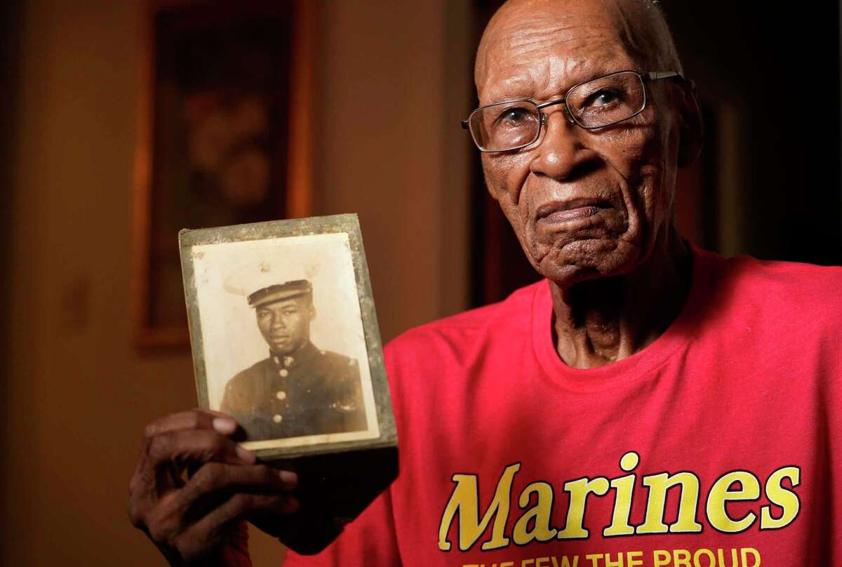 Arthur Jackson, 99, holding a photo of himself in his Marine uniform is shown Friday, July 9, 2021 in Houston. Serving from 1943 through 1946 Jackson was one of the original Montford Point Marines. He will receive a replica Montford Point Marines Congressional Gold Medal on Saturday. The Montford Point Marines were granted en masse the Congressional Gold Medal in 2012.