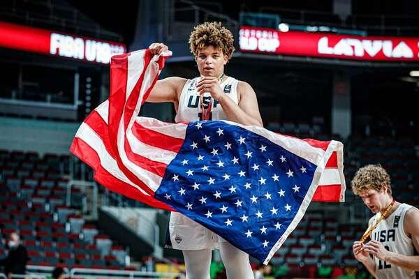 Port Arthur's Kenneth Lofton Jr. holds the American flag after winning gold on Sunday at the U-19 FIBA World Cup in Riga, Latvia.