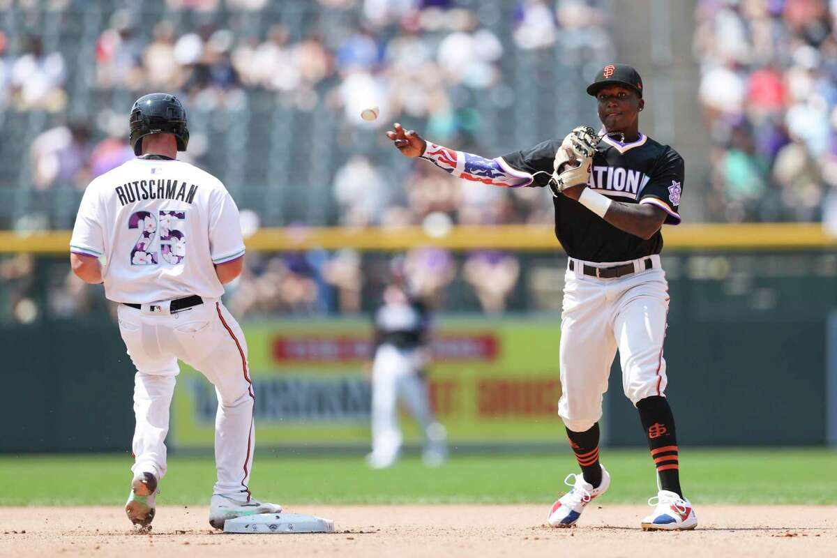 Marco Luciano, right, of the National League, throws out a runner at first base during the third inning of the MLB All Star Futures baseball game, Sunday, July 11, 2021, in Denver. (AP Photo/Gabe Christus)