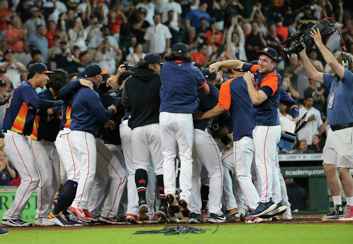 Houston Astros players celebrate second baseman Jose Altuve (27) in a circle after Altuve hit a walk off three-run home run and the Astros defeated New York Yankees 8-7 in a MLB game Sunday, July 11, 2021, from Minute Maid Park in Houston.