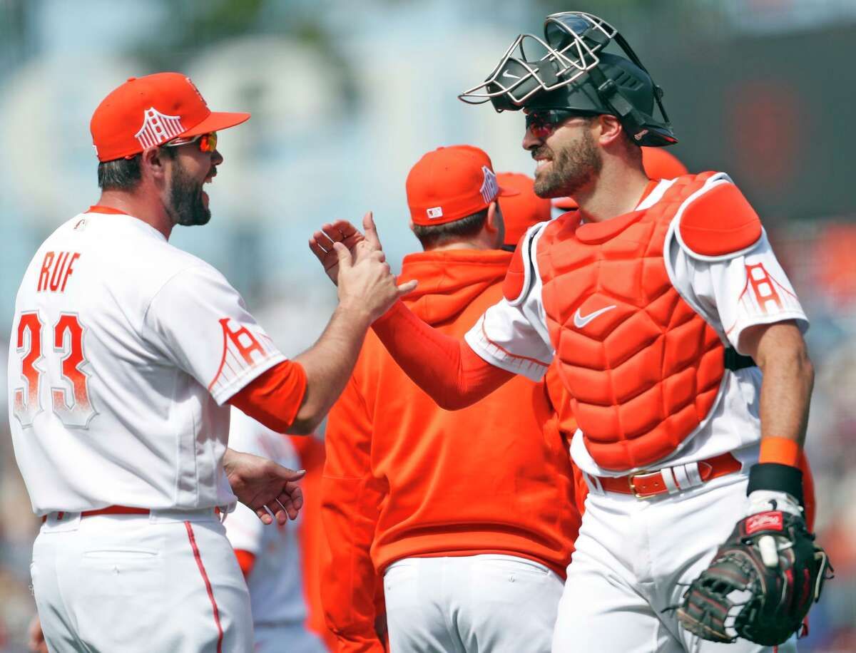 San Francisco Giants' Darin Ruf and Curt Casali celebrate 3-1 win over Washington Nationals in MLB game at Oracle Park in San Francisco, Calif., on Sunday, July 11, 2021.