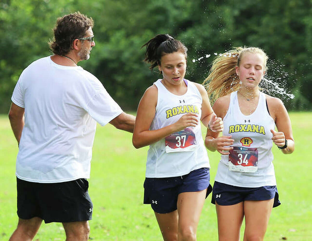 Roxana coach Scott Edwards (left) cools off Shells runners Olivia Mouser (right) and Jessi Ponce during a season-opening meet on a hot day in August last season at the Bethalto Sports Complex. Edwards is the 2020 Telegraph Small-Schools Girls Cross Country Coach of the Year.
