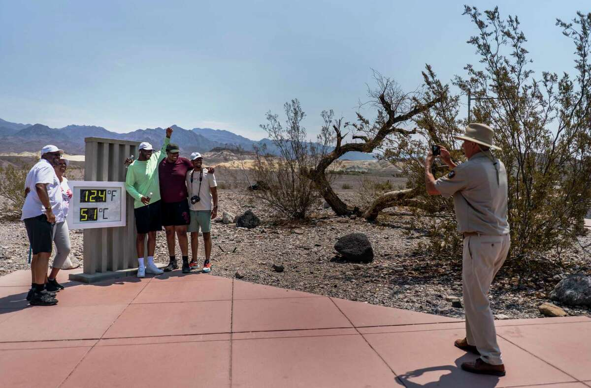 With record-setting heat expected Saturday, tourists like the Osborne family from Memphis stopped by the thermometer in California's Death Valley National Park.
