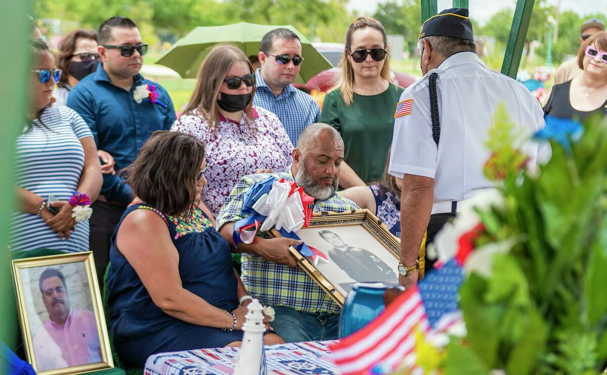 Surrounded by family, David Fuentes Jr. receives a portrait of his father, Korean War Navy Veteran David Fuentes Sr., from the American Legion Post 59 Honor Guard, Tuesday, July 6, 2021, at the Calvary Catholic Cemetery during a Welcome Home Graveyard Service with military honors. Fuentes Sr.'s remains were relocated to Laredo after 32 years.