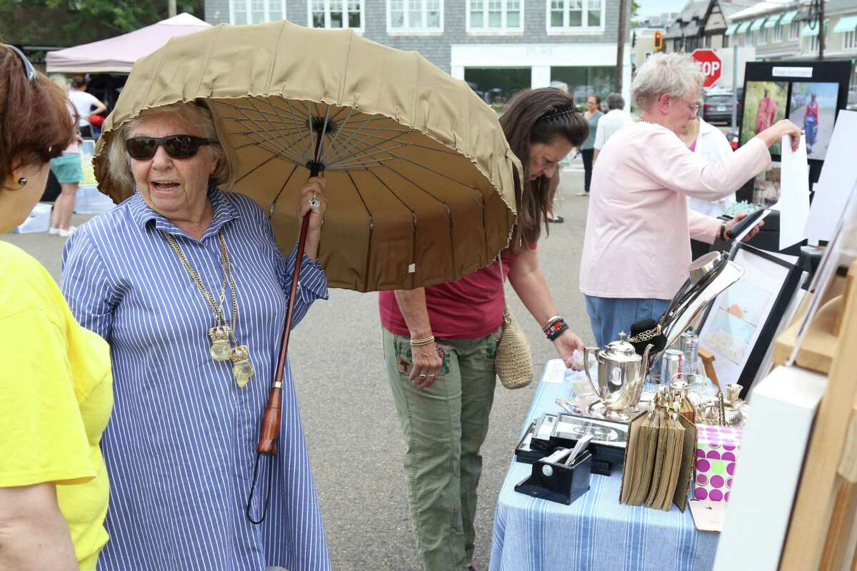 Artist Nina Bentley of Westport wards off the rain at the Artist Collective of Westport's trunk show at the parking lot by Jesup Green.