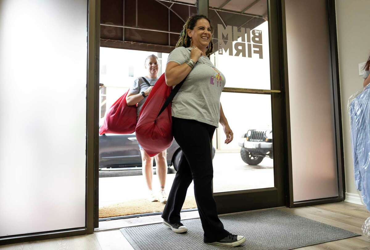 Miki Rankin, 'folding fairy' of The Laundry Fairy prepares to deliver laundry at The Bihm Firm, PLLC, Friday, July 9, 2021, in downtown Conroe. The Laundry Fairy started over three years ago offering their services throughout the majority of North Houston.