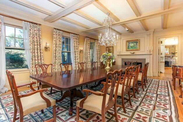 The dining room in the home on 49 Mountain Spring Roadcan seat at least 12 guests, and features a chandelier and a fireplace. Photo: Corrado Galizia