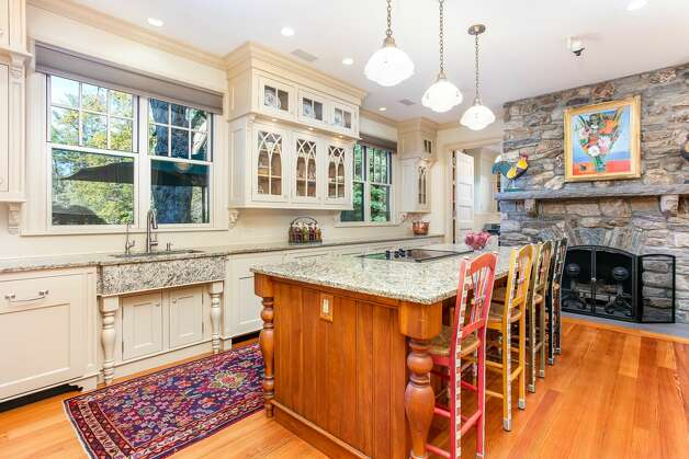 The kitchen in the 49 Mountain Spring Road homehas a large kitchen with a center island and stone fireplace. Photo: Corrado Galizia