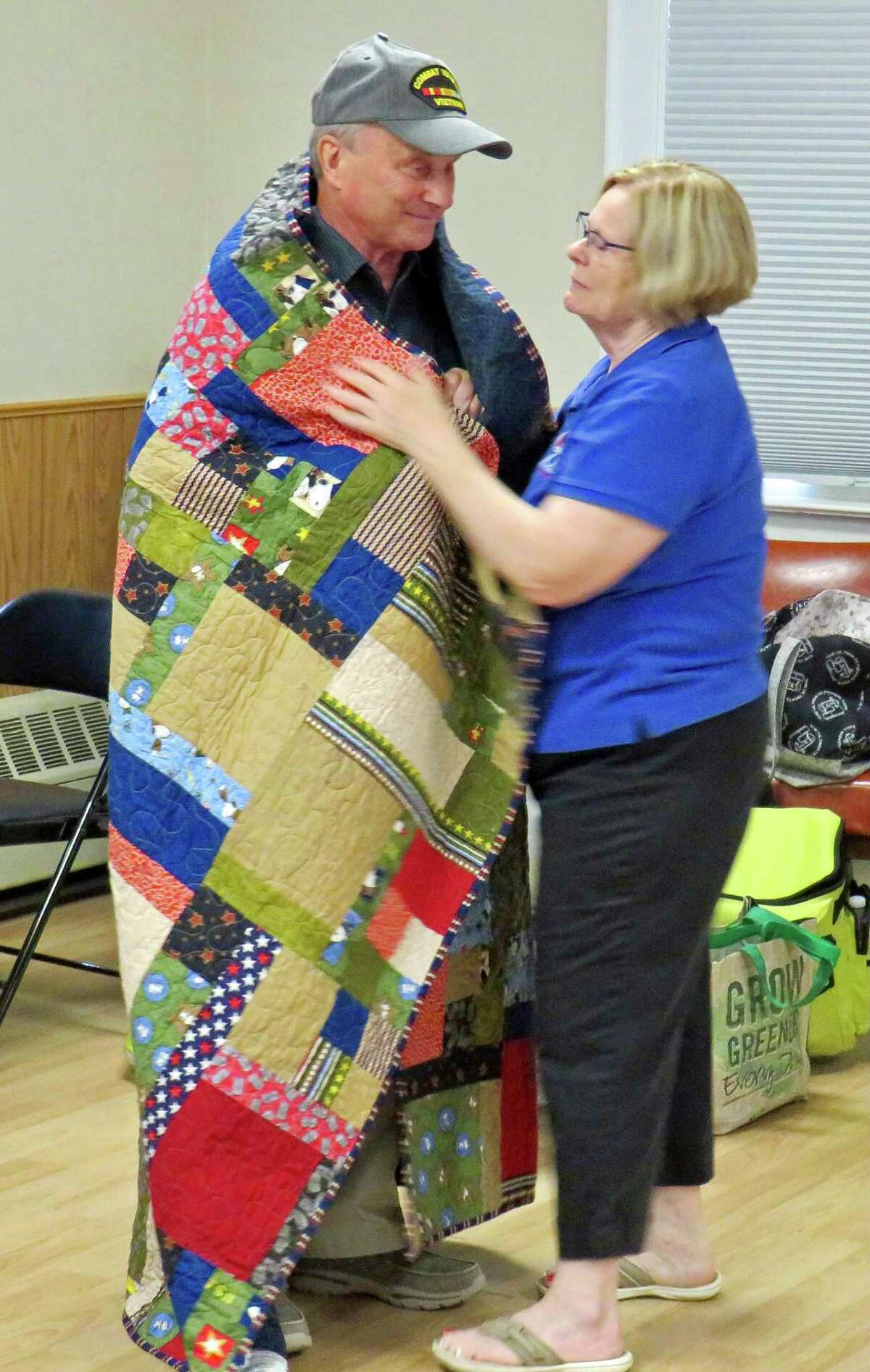 Vietnam Army veteran Robert Shirley accepting quilt from Nancy Burns from the Quilts of Valor Foundation.