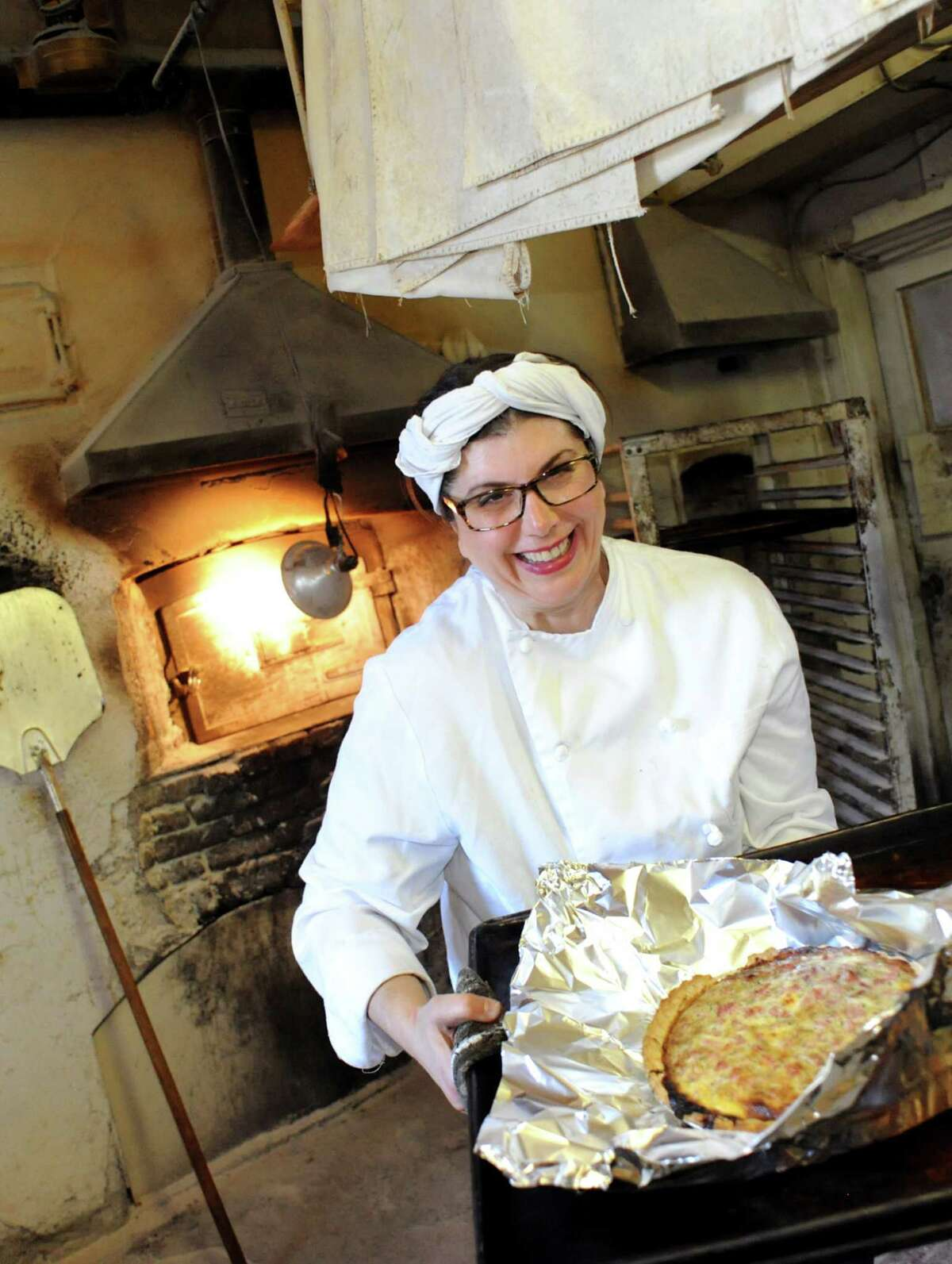 Maria Perreca Papa takes a ham pie from the oven at Perreca's Bakery in Schenectady in 2013. (Cindy Schultz/Times Union)