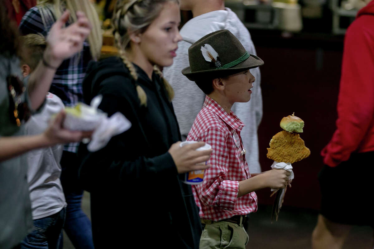 Festival attendees make their way through vendors with food in hand during Wurstfest at Landa Park in New Braunfels, Texas, on Nov. 3, 2019.