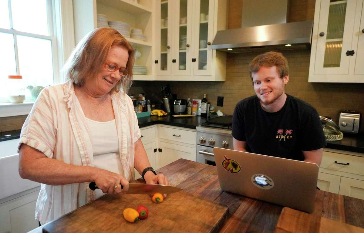 Helena Michie and her son, Paul Michie-Derrick, talk in the kitchen at their home Friday, July 9, 2021 in Houston. Because of the Covid-19 pandemic, young adults have been living with their parents in record numbers.