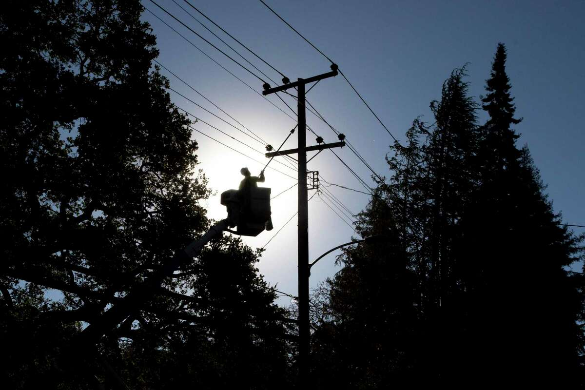 PG&E line inspector Kevin Ogans works to clear lines so crews can begin removing a tree that crashed into live power lines along Mountain Boulevard in the Montclair Village neighborhood of Oakland in October.