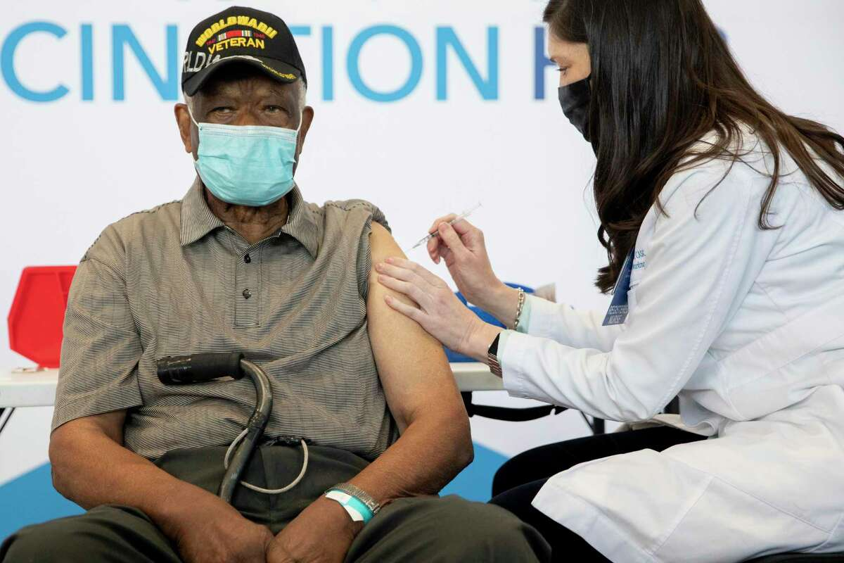 Ezekiel Logan, a 96-year-old World War II veteran, receives his first dose of the Pfizer vaccine at the Moscone Center mass vaccination clinic in San Francisco, Calif. Thursday, February 4, 2021.