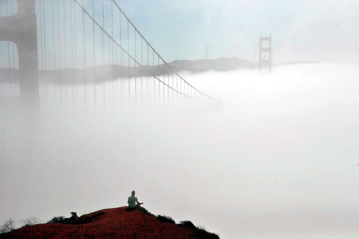 With the fog shrouded Golden Gate Bridge in front of him, Ivan Gushchin of Citrus Heights meditates at Marin Headlands in Sausalito, Calif. While parts of the Bay Area sweltered in the midst of yet another heat wave this weekend, San Francisco's high temperatures flirted with historic lows for July.