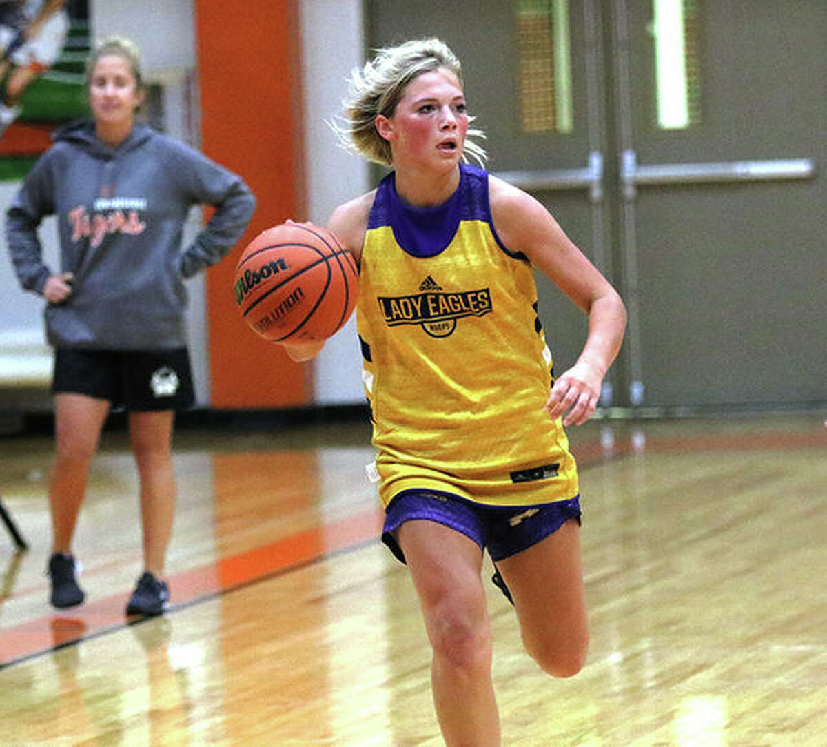 CM senior Kelbie Zupan pushes the ball upcourt while Edwardsville coach Caty Happe (left) watches from her team's bench during a June 29 summer game in Edwardsville.