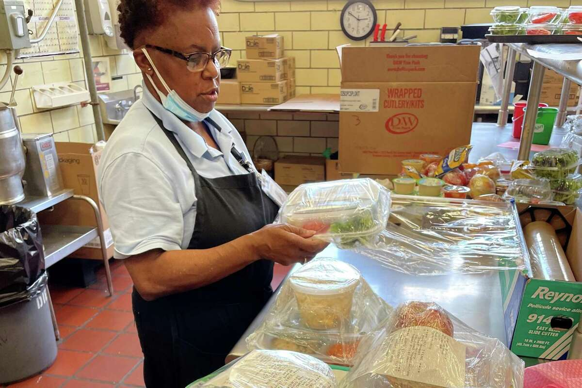 Bridgeport Hospital catering attendant Queen Davis helps cook and pack medically-tailored meals for patients in the hospital Complex Care Program. The program manages patients with multiple medical and social challenges that put them at risk for frequent hospitalization.