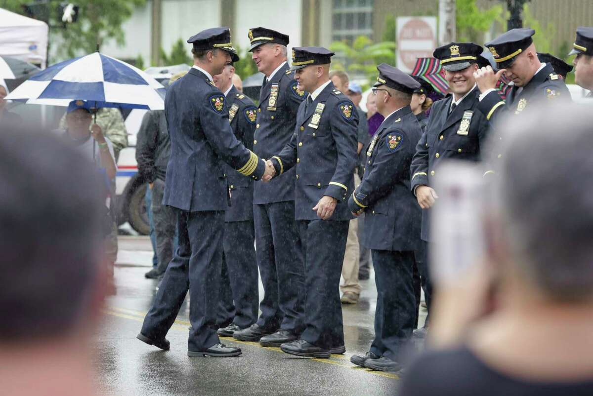 Troy Police Chief Brian Owens, left shakes hands with fellow officers during a ceremony to mark the chief's retirement on Monday, July 12, 2021, in Troy, N.Y. (Paul Buckowski/Times Union)