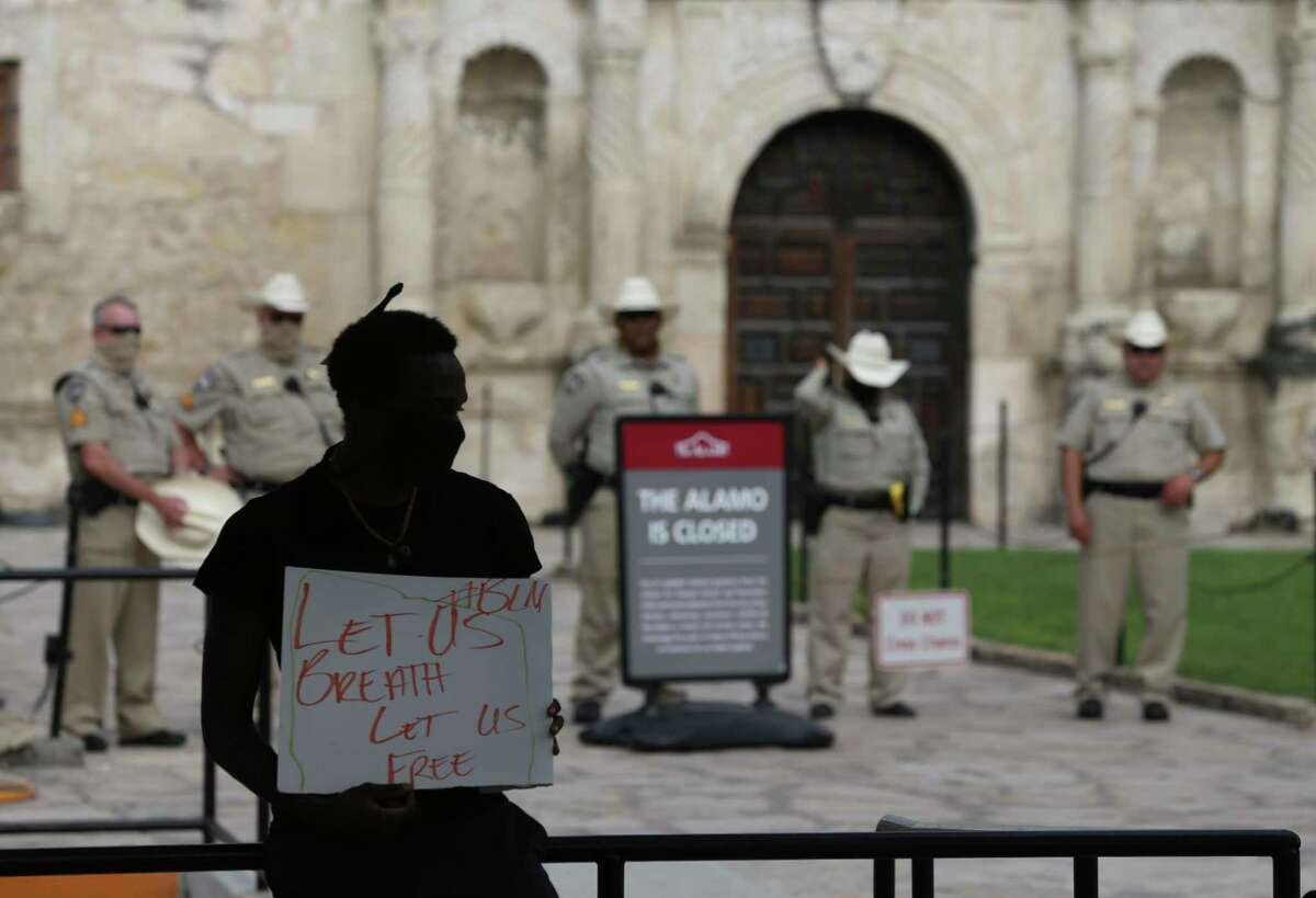 Isaiah Adams holds a sign in front of the Alamo, Sunday, May 31, 2020, during peaceful rally held after the murder of George Floyd in Minneapolis. A panel discussion on Tuesday will focus on slavery and racial inequities that were prevalent in Texas in the 1800s.