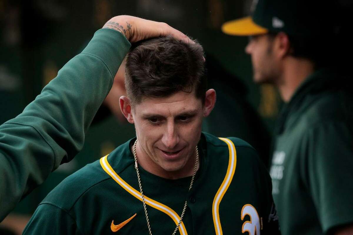 Frank Schwindel (45) gets a pat on the head from Sean Manaea (55) after hitting his solo homer in the second dinning as the Oakland Athletics played the Texas Rangers at the Coliseum in Oakland, Calif., on Wednesday, June 30, 2021.