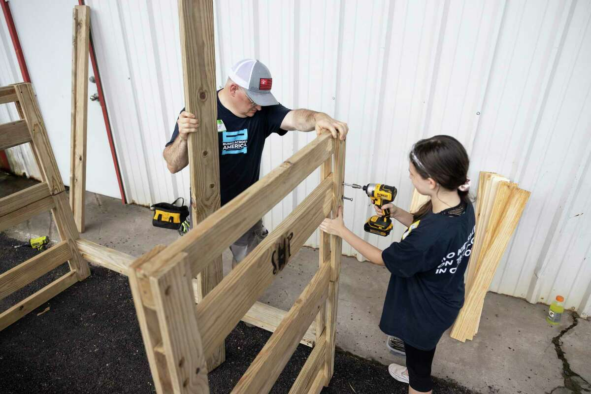 Mike Fortner, left, assists Addison Michel, 12, as she drills screws into a bunk bed during a volunteer bed-making event hosted by Sleep in Heavenly Peace held at Milstead Collision, Saturday, July 10, 2021, in Spring. Sleep in Heavenly Peace opened a chapter in Montgomery County in March of 2021 and has given out over 45 beds to children in need.