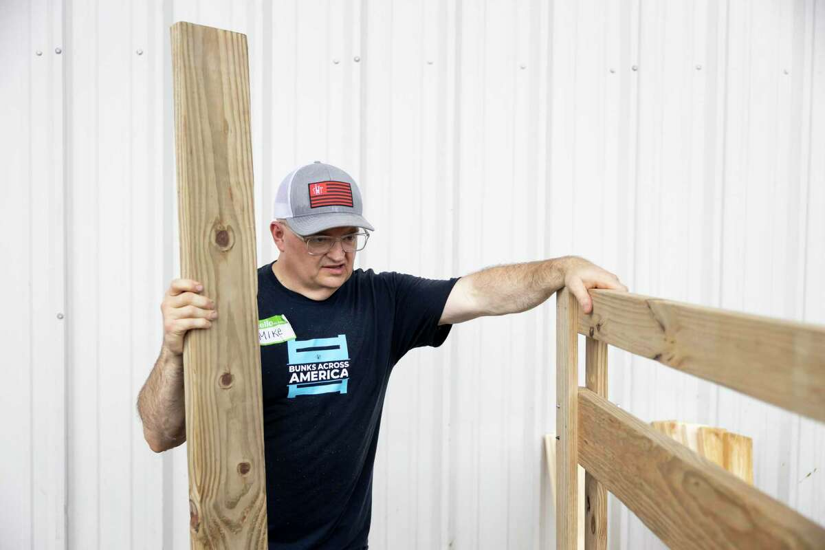 Mike Fortner holds onto a bunk bed as it's put together during a volunteer bed-making event hosted by Sleep in Heavenly Peace held at Milstead Collision, Saturday, July 10, 2021, in Spring. Sleep in Heavenly Peace opened a chapter in Montgomery County in March of 2021 and has given out over 45 beds to children in need.