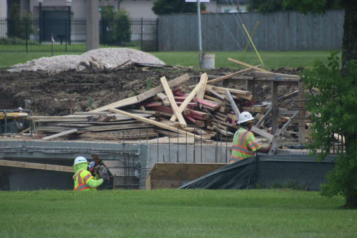 Workers are constructing a bridge over a canal that flows under Friendswood Lakes Boulevard.