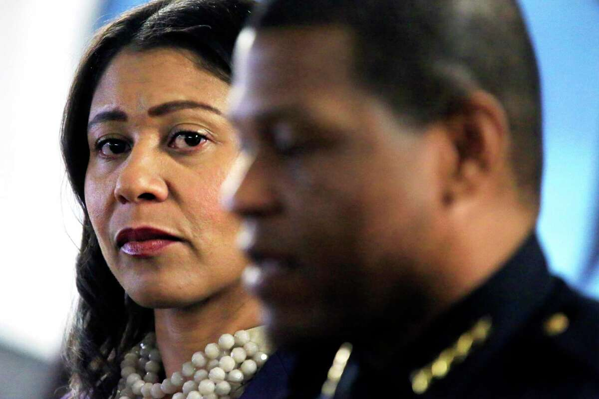 Acting Mayor London Breed, left, listens to Police Chief Bill Scott speak during a gun buy-back press conference in San Francisco, Calif. Breed and Scott sought to push back against the growing national narrative that crime in San Francisco is running rampant, citing the latest city crime statistics.