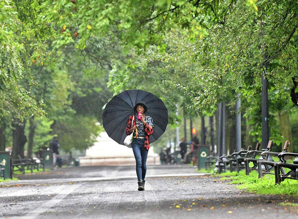 This summer's must have accessory is an umbrellas. More than 5 inches of rain have fallen in the Capital Region. In this photograph, a pedestrian sips from a water bottle with an umbrella as rain fell in Albany's Washington Park on Monday. (Lori Van Buren/Times Union)