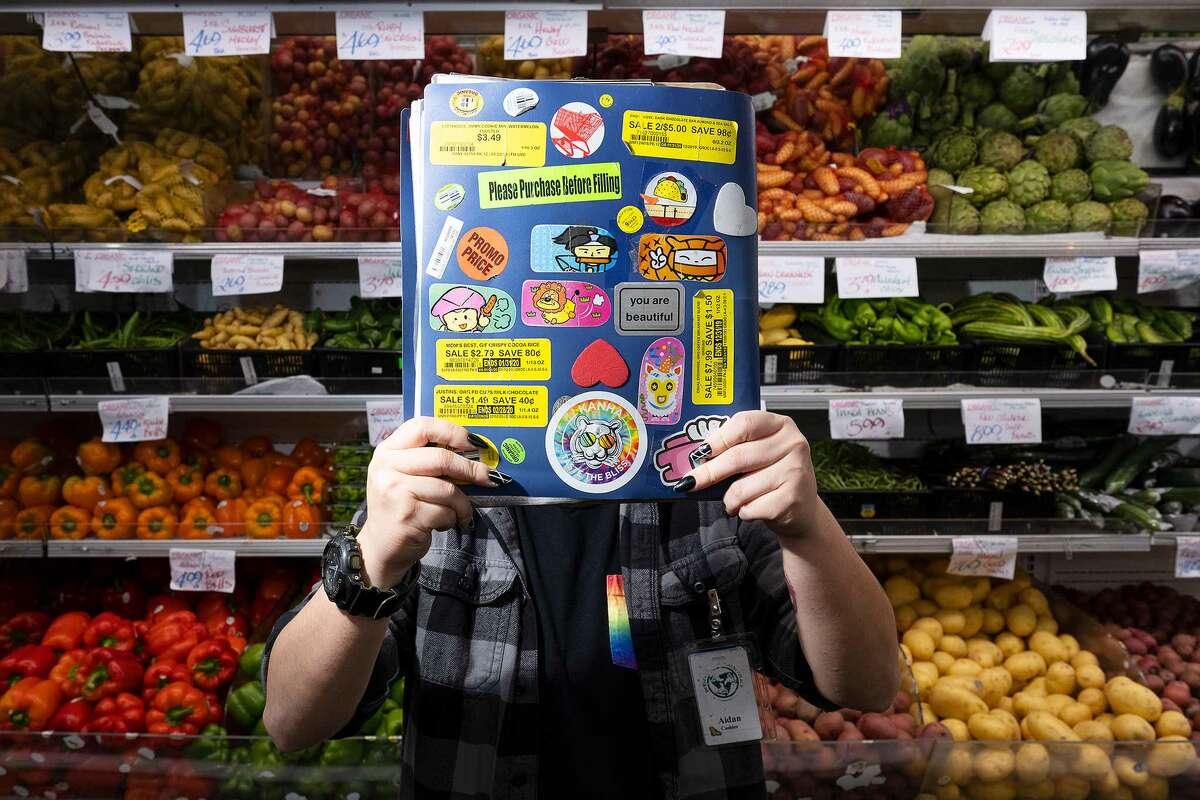 Aidan Mieu, a cashier at Berkeley Bowl, behind their book of produce codes.