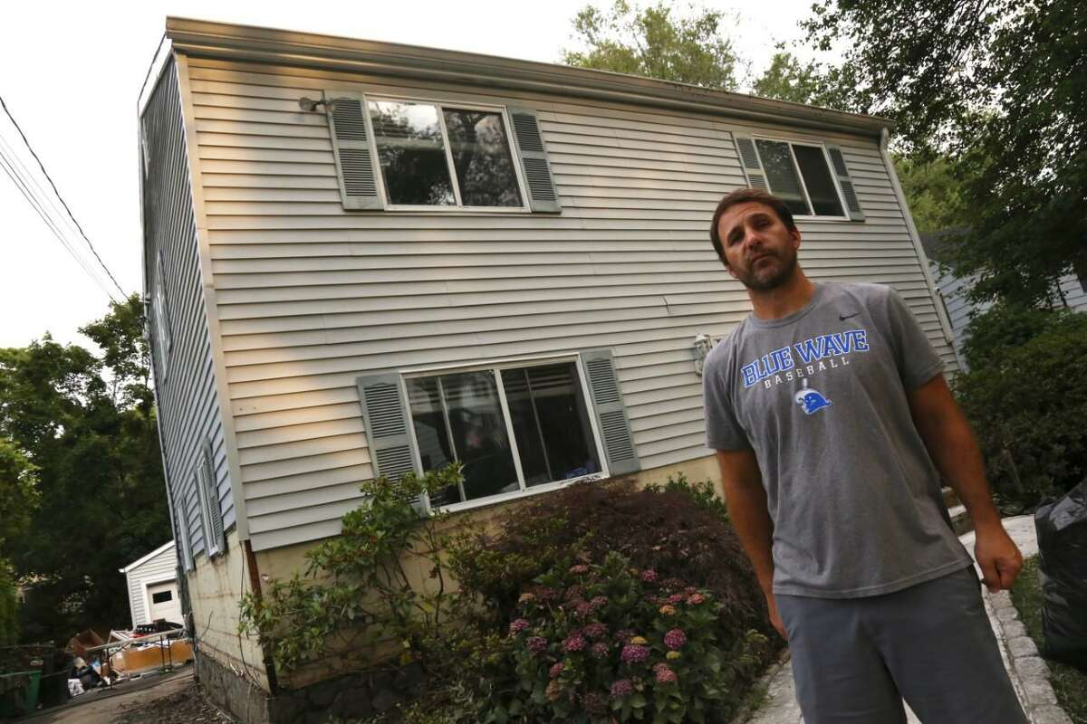 Brian Valentine stands by his Crimmins Road home, which was devastated by flooding and accompanying sewage and waste water, which rose to two feet inside.