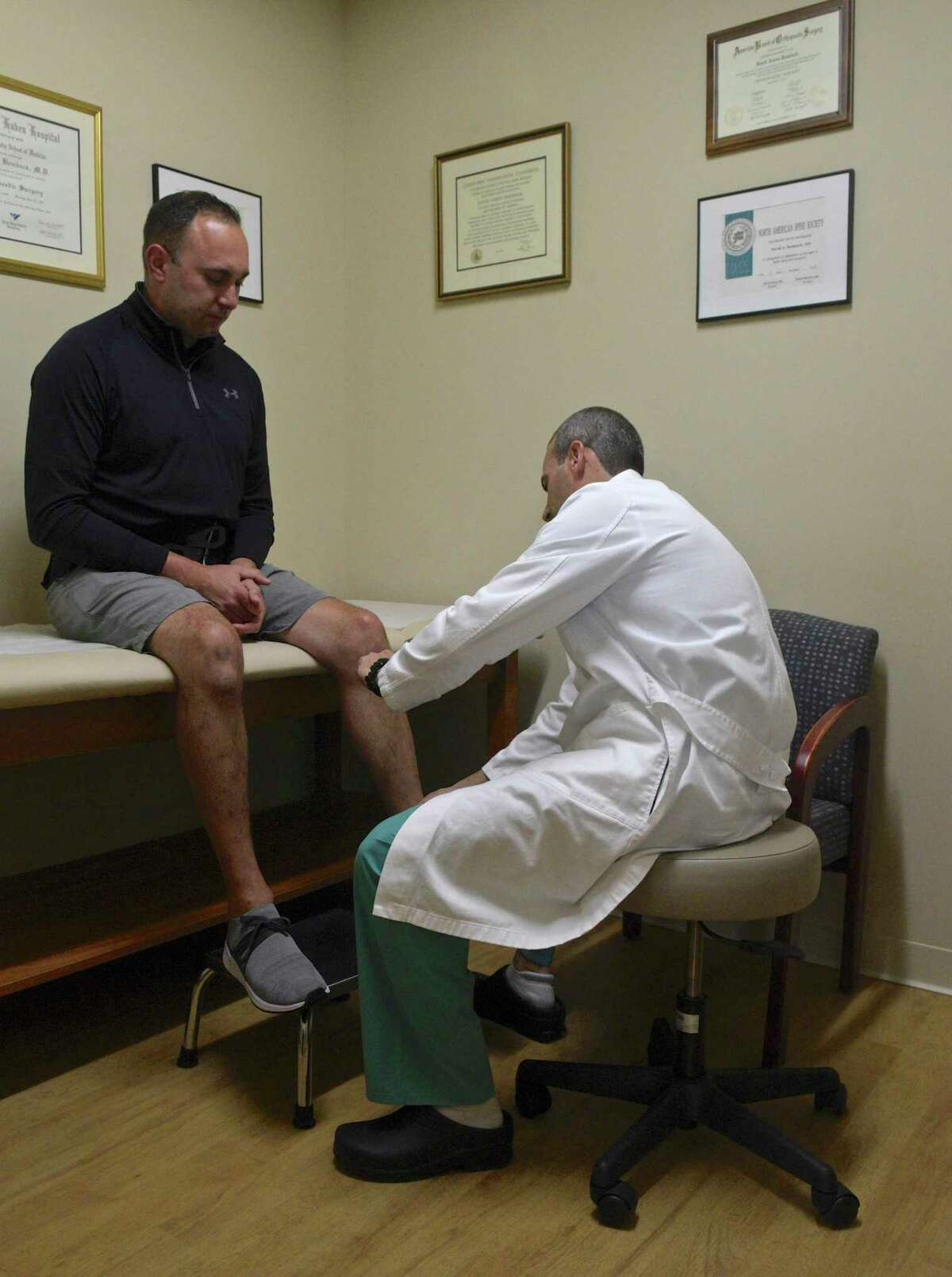 Joe Esposito talks with Dr David Bomback during a follow-up to his back surgery. Esposito recently had ground breaking back surgery, the first one done in the state, by Dr Bomback. Friday, July 9, 2021, Danbury, Conn.