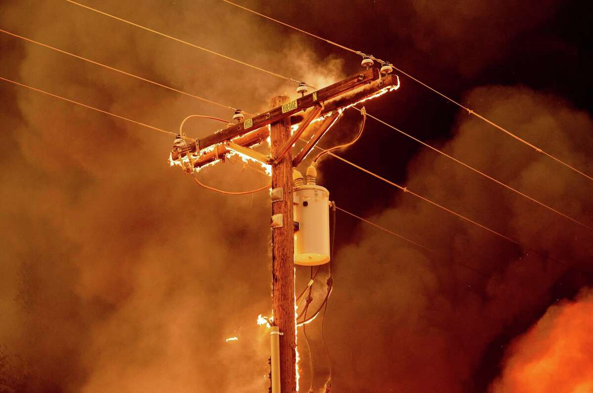 Fire burns along a power pole as the Sugar Fire, part of the Beckwourth Complex Fire, tears through central Doyle, Calif., on Saturday, July 10, 2021.