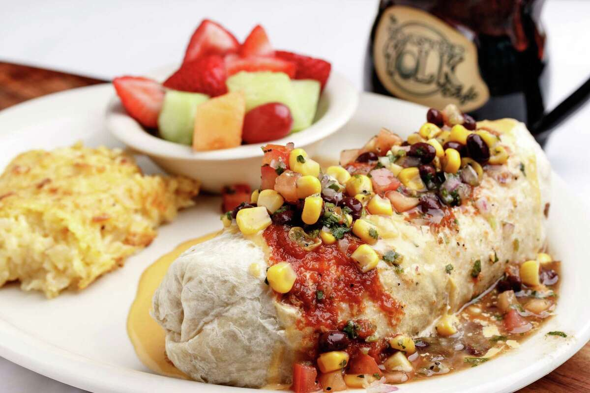 """The Toasted Yolk Cafe's breakfast burrito is """"Three eggs scrambled with green chiles, onion, potatoes, sausage, and cheddar cheese. Wrapped in a large tortilla topped with salsa, homemade queso, and topped with pico de gallo."""""""