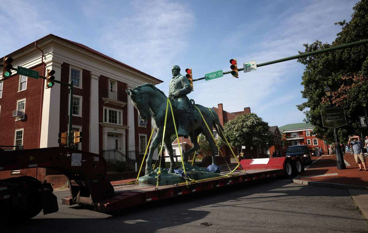 """A flatbed truck carries a statue of Confederate General Robert E. Lee from the Market Street Park July 10, 2021, in Charlottesville, Virginia. Initial plans to remove the statue four years ago sparked the infamous """"Unite the Right"""" rally where 32 year old Heather Heyer was killed. A statue of Confederate General Thomas """"Stonewall"""" Jackson in the Charlottesville and Albemarle County Courthouse Historic District is also scheduled to be removed this weekend. (Photo by Win McNamee/Getty Images)"""