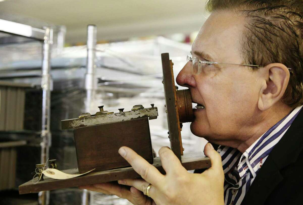 """David Monroe, founding chair of the San Antonio Museum of Science and Technology, demonstrates how to use a late 1800s Bell """"camera"""" telephone. It's part of the collection at Foxworks, a private area area that houses tech artifacts separate from the main museum. Most are owned by Monroe, who holds patents on several inventions - including the cell phone camera. With over 37,000 square-feet of space, Foxworks has become a hub for several tech companies."""