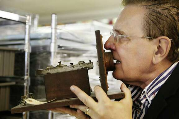 """David Monroe, founding chair of the San Antonio Museum of Science and Technology, demonstrates how to use a late 1800s Bell """"camera"""" telephone. It's part of the collection at Foxworks, a private area area that houses tech artifacts separate from the main museum. Most are owned by Monroe, who holds patents on several inventions — including the cell phone camera. With over 37,000 square-feet of space, Foxworks has become a hub for several tech companies."""