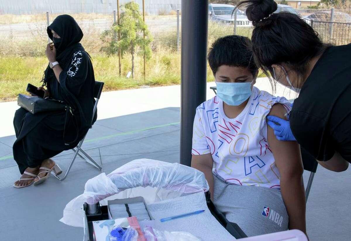 Salamoyu Yahaya of Cupertino waits after her shot as Kini Evaimalo, 12, receives his vaccination at East Palo Alto's EPAcenter.