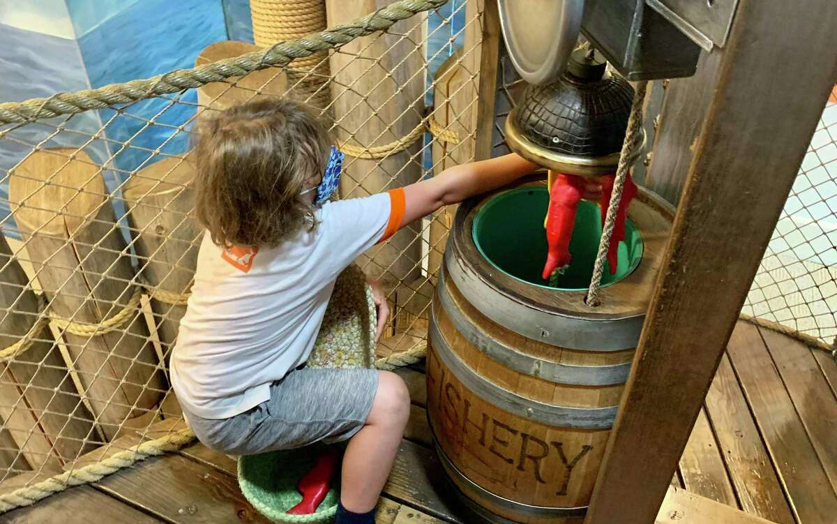 Taylor Landers-Haddad, 7, loads fish into a barrel in the nautical-themed room at Kidcity Children's Museum in Middletown Monday.