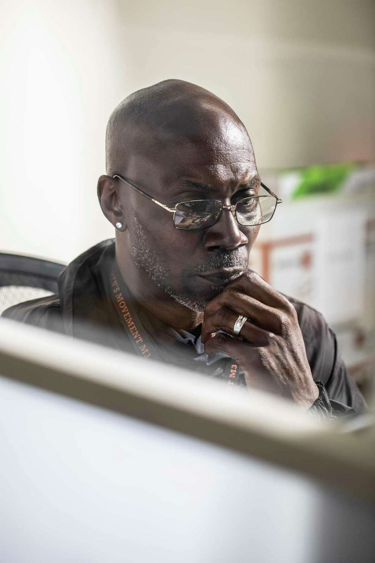 Charles Ryan, a case manager at the San Francisco Pretrial Diversion Project, works in his office cubicle in San Francisco, California Tuesday, July 6, 2021. Ryan, a San Francisco native, was jailed for 6 years while awaiting trial for a 2009 robbery and assault he did not commit.