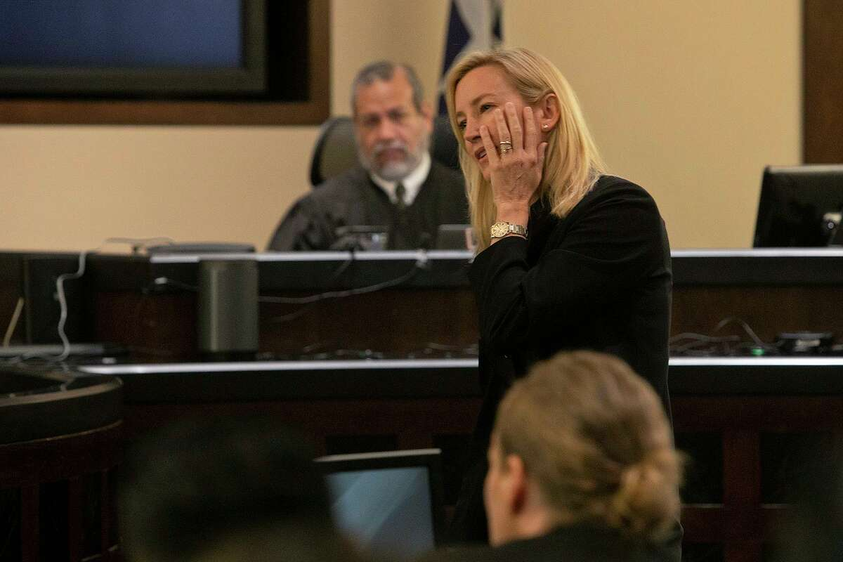 As she speaks to the jury, prosecutor Tamara Strauch touches her cheek to describe where Detective Benjamin Marconi was shot. Watching is presiding Judge Ron Rangel.