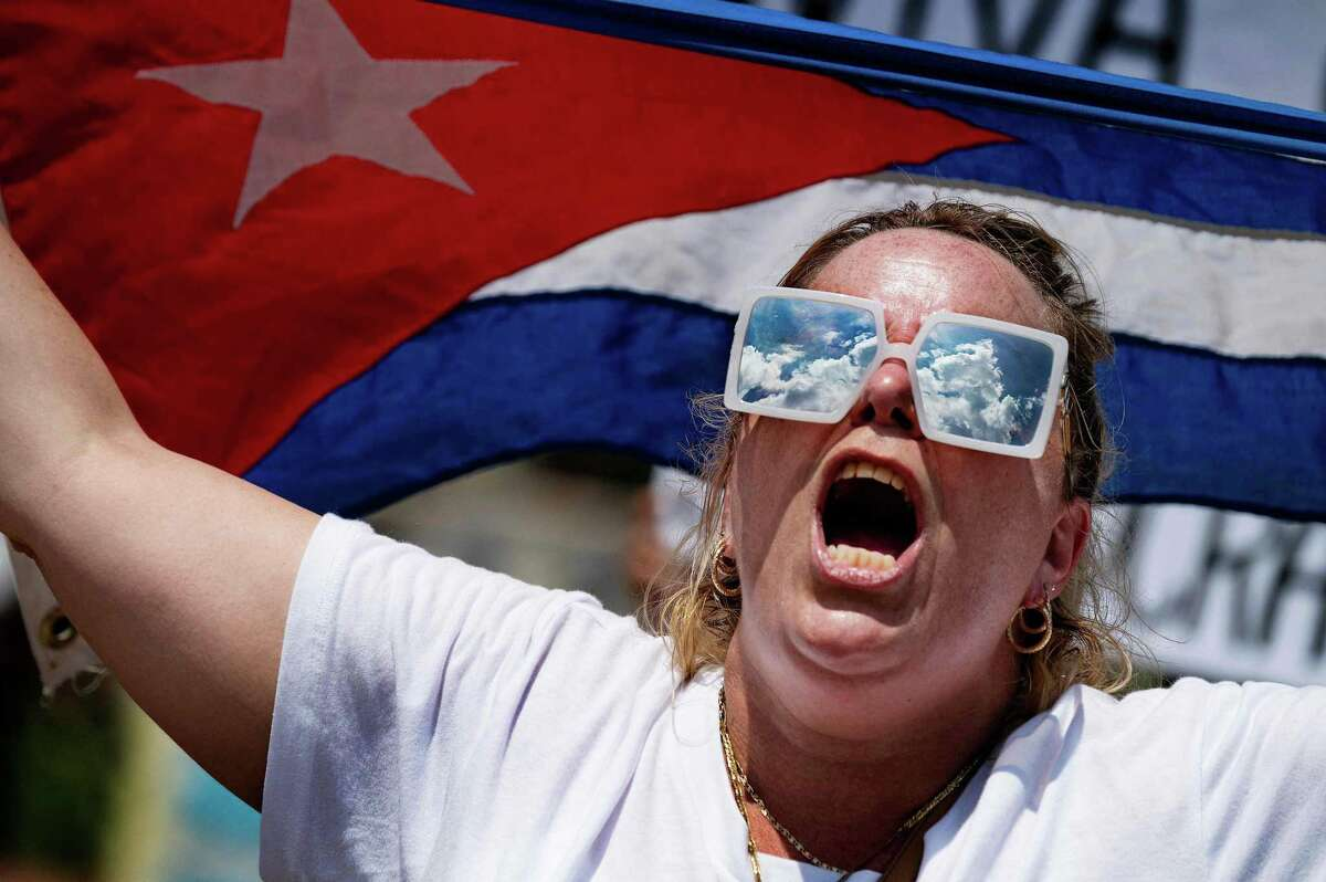 """A demonstrator holds up the Cuban flag while protesting in front of the White House in Washington, DC, on July 12, 2021. - Historic mass protests in Cuba have thrust onto US President Joe Biden's priority list an issue on which he was content to go slow and, experts say, will likely doom near-term prospects of a fresh opening. Biden issued a statement to voice solidarity with """"the Cuban people and their clarion call for freedom,"""" and the White House warned authorities not to use force after thousands poured onto the streets Sunday amid the worst economic crisis in decades. Cuba has seen a whiplash in US policy with former president Barack Obama normalizing relations at the end of his term, declaring that a half-century of efforts to topple the regime had failed, and then his successor Donald Trump reimposing sweeping economic pressure. (Photo by JIM WATSON / AFP) (Photo by JIM WATSON/AFP via Getty Images)"""