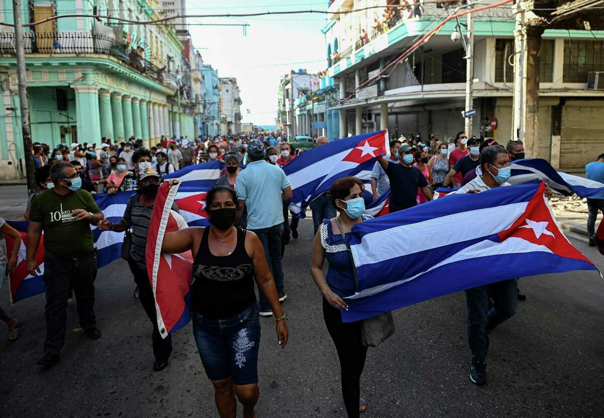 """People take part in a demonstration to support the government of the Cuban President Miguel Diaz-Canel in Havana, on Sunday, July 11, 2021. Thousands of Cubans took part in rare protests Sunday against the communist government, marching through a town chanting """"Down with the dictatorship"""" and """"We want liberty."""" (Yamil Lage/ AFP/Getty Images/TNS)"""