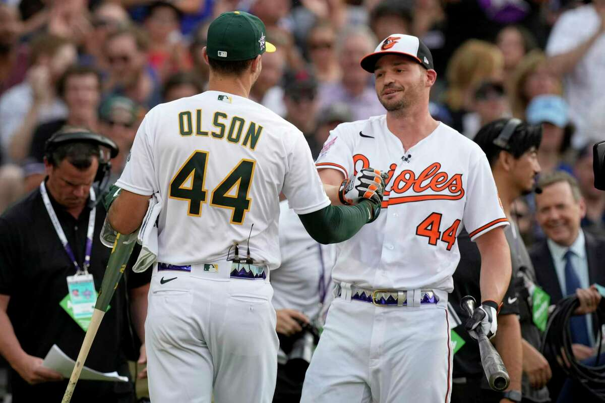 American League's Trey Mancini, of the Baltimore Orioles, right, greets American League's Matt Olson, of the Oakland Athletics, during the first round of the MLB All Star baseball Home Run Derby, Monday, July 12, 2021, in Denver. (AP Photo/David Zalubowski)